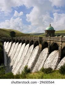 Water overflowing a dam, Craig Goch reservoir, Elan Valley Wales.