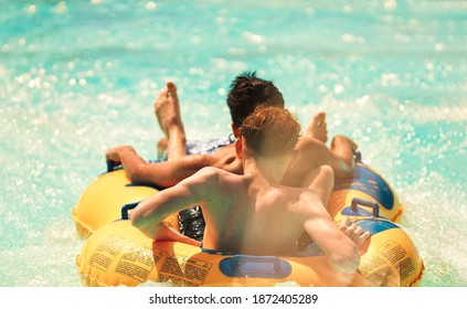 Water park adventure aqua park with cool people having fun on the water slide with friends and familiy in the aqua fun park glides playing happy in the sunlight and water splashes are all over the sky