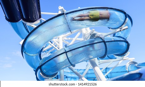 Water park slide pipe or float tube with the man floating down it on the cruise liner ship in the open sea