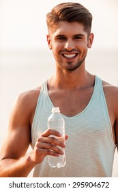 Water is a part of healthy training. Cheerful young muscular man holding a bottle and smiling while standing outdoors