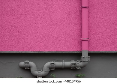 Water pipe on pink textured wall