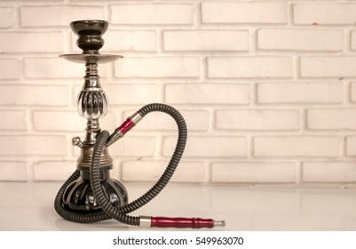 Water pipe smoking, Baragu, Hooka, Shisha on table white brick wall background