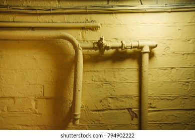 Water pipeline in tunnel of residential old building. The brick wall and pipes, the faucet are painted yellow