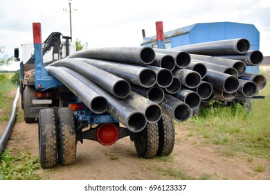 Water pipes hanging from the trailer of a truck standing on the road