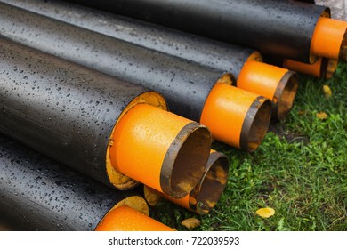 Water pipes with insulation lie on the grass