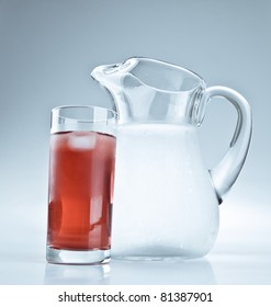 Water pitcher and a glass of red lemonade