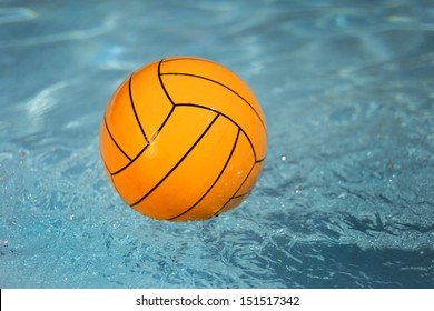A water polo ball floating on the water in a pool.