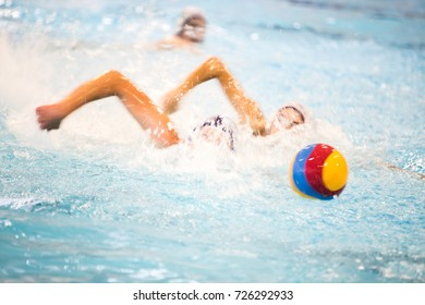 Water polo players dashing for a ball