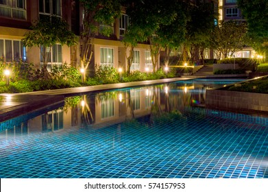 Water pool in courtyard in apartment complex of condominium. Evening and night view with illuminated of water