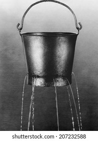 Water poring through holes in bucket (b&w)