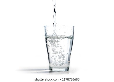 water is poured into a drinking glass, isolated on a white background with copy space