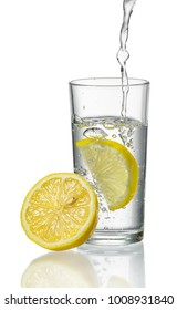 Water is poured into a glass with fresh lemons isolated on white