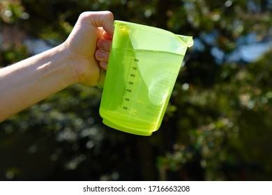 Water is poured out of a green cup in sunlight.