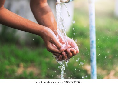 water pouring in faucet  on hand child in park