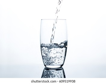 Water pouring into the clear glass, standing on light table with mirror effect