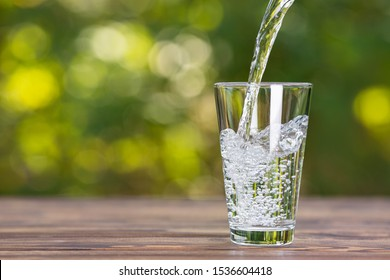 water pouring into glass on wooden table outdoors