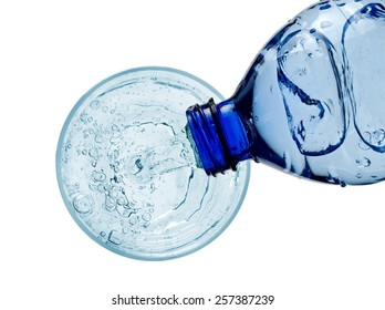 Water pouring into a glass from a plastic bottle, top view