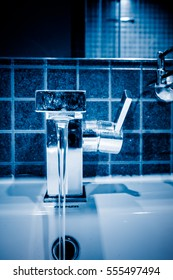 Water pouring from modern faucet in bathroom,blue tone.