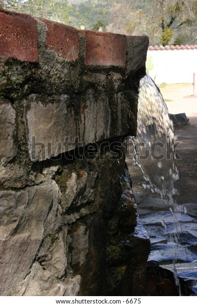 water pouring off brick ledge