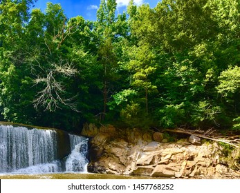 Water pouring over a dam in a stream at an abandon mill. Rock formations on riverbank, downed tree, bright green deciduous forest and local swimming hole on a hot summer day in Virginia