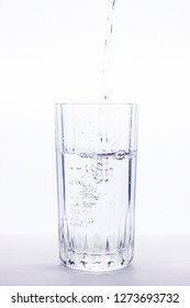 water pours into a clear glass, on a light background, a glass of water