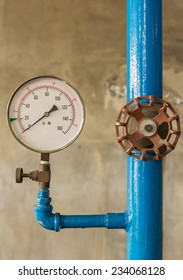 Water pressure meter installed on a blue pipe
