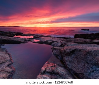 A water puddle on the rocky shoreline cliff reflecting the fiery sunrise over the ocean