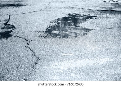 water puddles with raindrops and water circles on cracked wet asphalt road