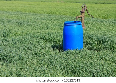Water pump and a blue barrel on the field