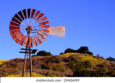 Water pumping windmill with a hill and blue sky in the background.