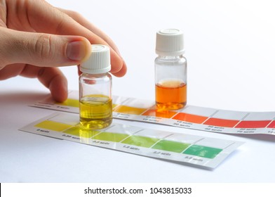 Water quality testing. Man determining water characteristics by comparing the color of liquid in testing vials with attached color scales