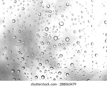 Water rain drop on window glass with white grey cloudy background.