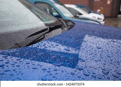Water rain drops on a car winshield windscreen and bonnet hood outside