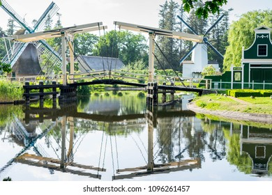 Water reflection of bridge, wind mills and a traditional dutch building at Arnhem open air and national heritage  museum, in Arnhem, Netherlands