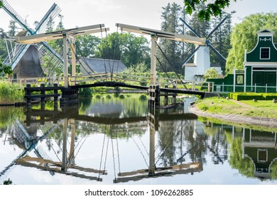 Water reflection of bridge, wind mills and a traditional dutch building at Arnhem Open - air and national heritage  museum, in Arnhem, Netherlands