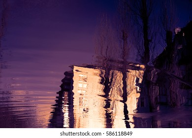 Water reflection house in the puddle. Apartment building is reflected in the spring floods with a purple violet sky and the bare trees without leaves. The forms of objects and plants distorted.