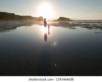 Water reflection of mother and daughter in the beach