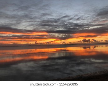 Water reflection of orange sky grey cloud in early morning light. Strong orange red glass background
