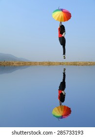 Water Reflection Rainbow umbrella woman and blue sky.Copy space