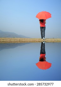 Water Reflection Red umbrella woman and blue sky.Copy space