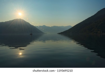 Water reflection of a sun rising over the hills early in the morning at the Bay of Kotor (Boka Kotorska) near Kostanjica, Montenegro