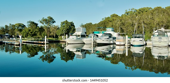Water reflections at a country marina/dock with boats in tropical water with blue sky backdrop. Bush setting for sailing and cruising vessels. Lake Macquarie, Australia.