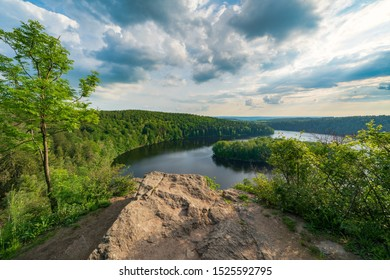 """Water reservoir """"Sec"""" in the Czech Republic, Europe.  View from nature reserve Oheb located in """"Zelezne hory"""". Little dramatic clouds over trees and water surface  a few hours before sunset."""