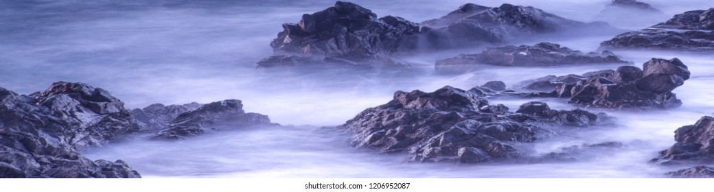 Water with rock nature photo with long exposure fog effect.Panorama or banner abstract color ocean background