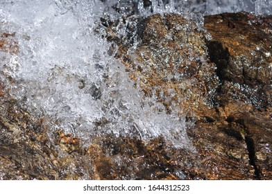 Water running over stone close up