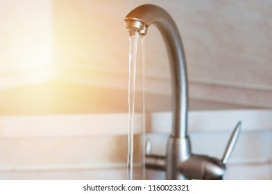 Water running from the tap of the sink in the kitchen. Warm light filter