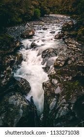 Water running through stream over dark rocks from water fall