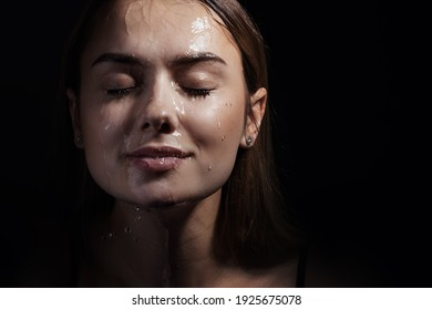 Water runs down my face. Portrait of a young beautiful woman