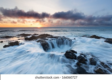 Water rushes into Thor's Well on the Pacific Ocean as the sun sets over Oregon.
