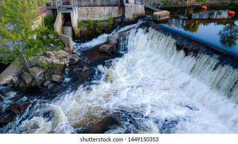 water rushing over dam near small power plant